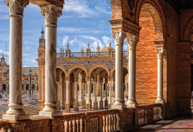 Marble columns, tall tower, and red stone architecture at the Plaza De Espana in Madrid, Spain.