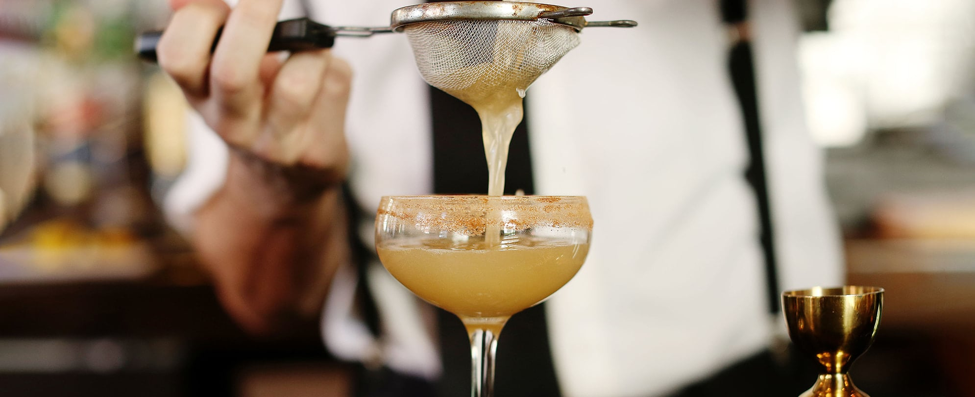 Bartender straining juice into a cocktail glass at a resort bar