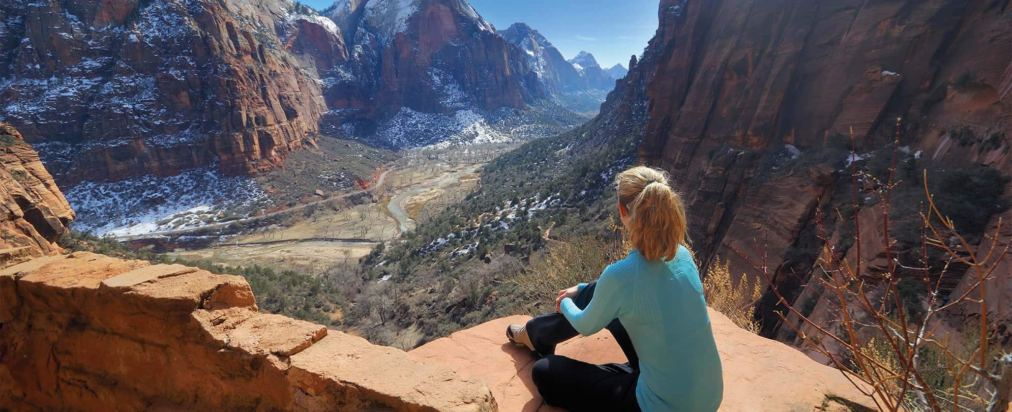 A woman sits on a rock overlooking Zion National Park in St. George, Utah