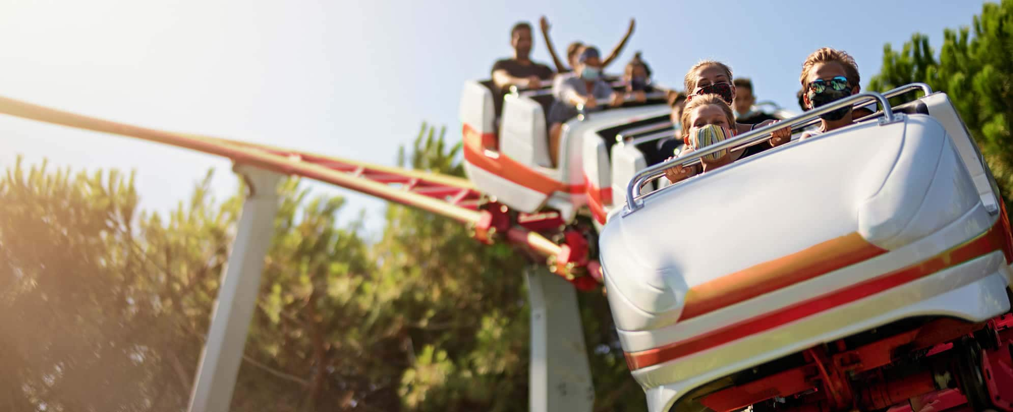 Three mask-wearing kids ride in the front car on a white and red roller coaster