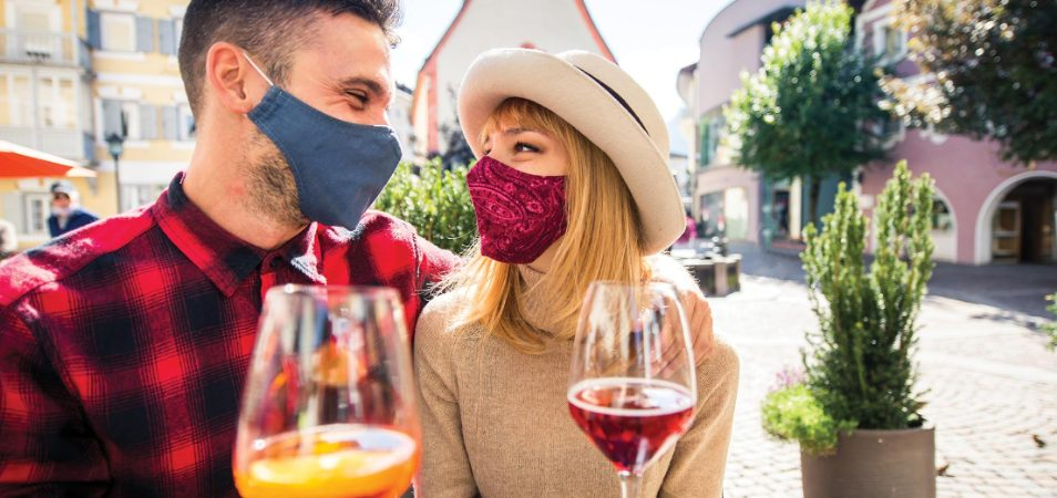 Masked man and woman drinking wine in a top drinking destination