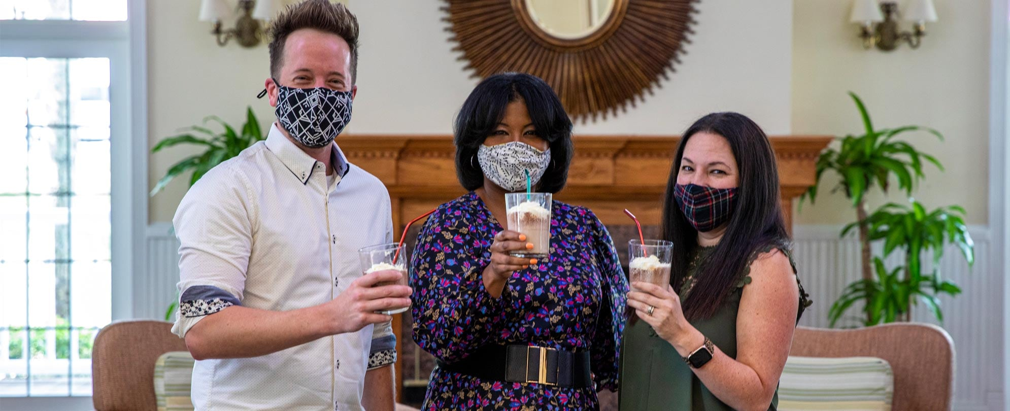 Three friends wearing masks and holding up coffee milkshake drinks with straws.