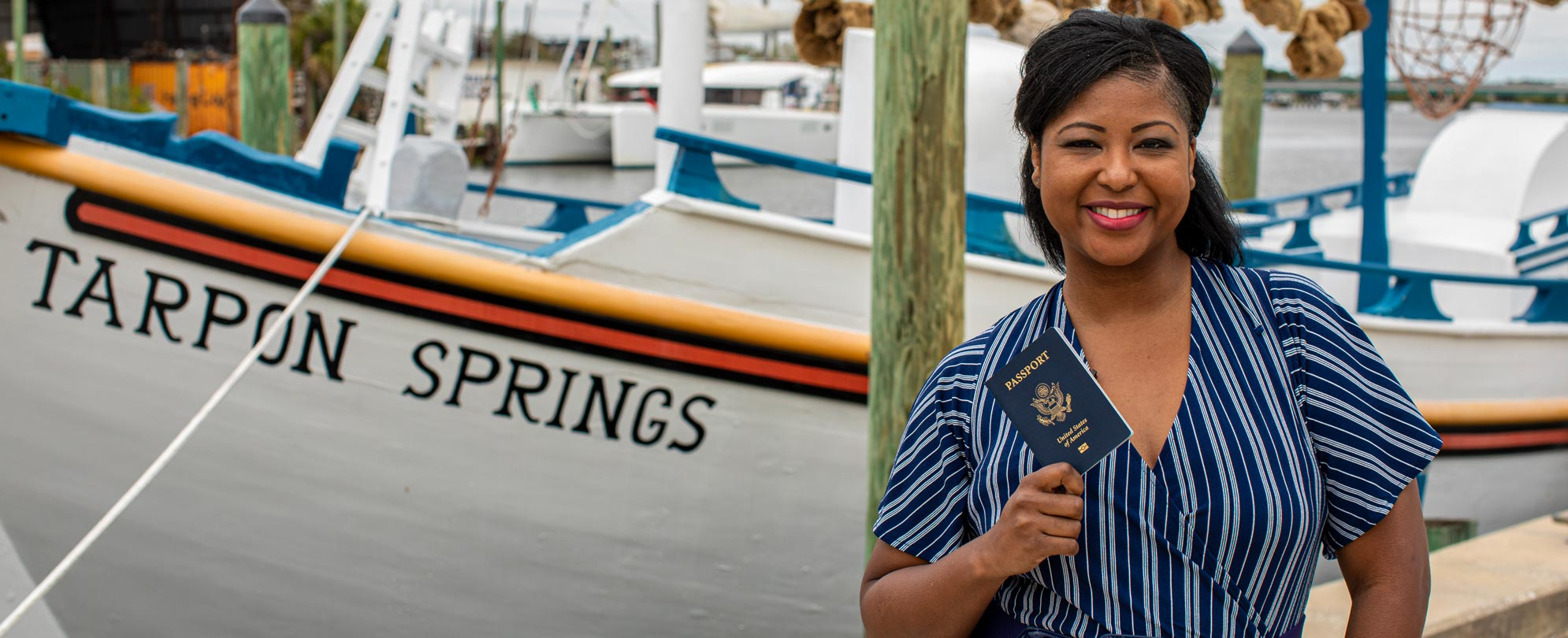A woman smiling and holding up a passport in front of a Tarpon Springs boat.