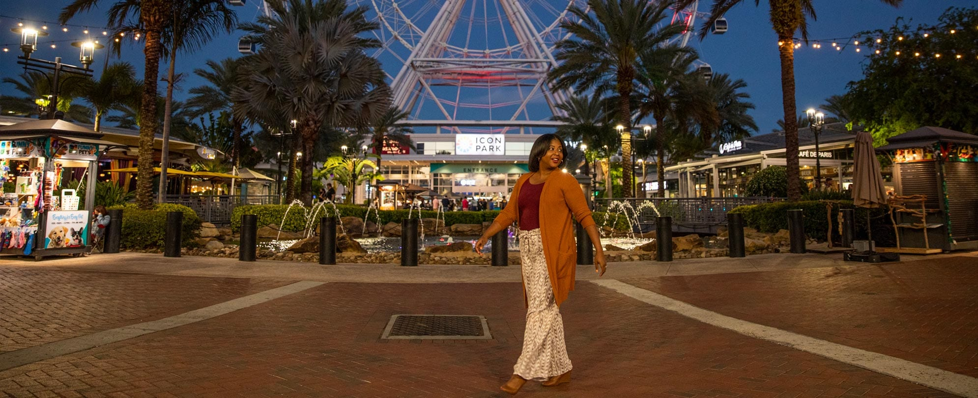 A woman walking through the courtyard of Icon Park in Orlando, Florida at dusk.
